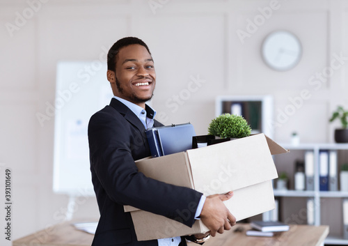 Happy black businessman moving office with box and his belongings - fototapety na wymiar