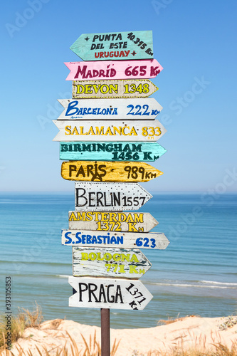 Colorful directions signs on the beach to different places of the world. Travel concept.