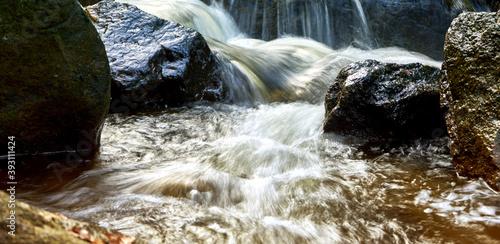 Papel de parede Closeup shot of a forest river creek flowing over wet irregular stones