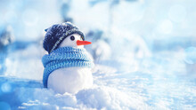 Little Snowman In A Hat And Scarf On The Snow On A Sunny Winter Day, Soft Selective Focus, Copy Space. Christmas Background Banner, Winter Holidays, Preparation For The Holiday