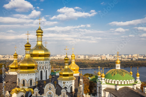 Fotografie, Tablou Beautiful yellow and gold domes of the Orthodox Church against the background of the blue sky and the city