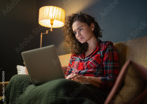 Cuadros en Lienzo A young modern woman with a laptop late at night sits on the couch and surfs the Internet, makes purchases, watches a video, writes