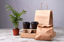 Coffee Cardboard Cups And Paper Packages. Eko Friendly Packing On The Wooden Table. Beautiful Plant In Flowerpot.
