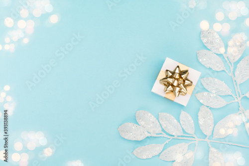 Fototapeta Christmas card - Xmas gold gift box and silver decorations on pastel blue paper background. obraz