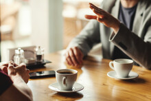 Closeup Hands Of Two Unrecognizable Male Business Partners Having Business Talk Over Espresso Coffee Sitting At Table In Cafe