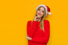 Portrait Of Cheerful Young Woman In Santa Hat And Red Sweater