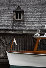 Modern Motor Vessel Moored Near Weathered Gray Wooden Boat Shed With Small Window At Waterfront