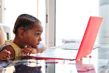 Multiethnic Mother And Child Sitting Together At Table And Watching Interesting Cartoon On Netbook While Relaxing At Home