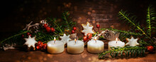 Four Lighted Small Candles For The Fourth Advent With Christmas Decoration On Dark Rustic Wood, Panoramic Format, Copy Space, Selected Focus