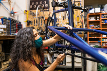 Side View Of Female Worker In Protective Mask Installing Break And Transmission Wires On Bicycle During Maintenance Service In Workshop