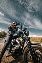 Low Angle Of Unrecognizable Male Rider In Leather Jacket And Helmet Sitting On Motorbike On Roadside Against Cloudy Sky In Countryside