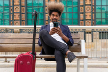 African Man In Suit Using His Mobile Phone Sitting In A Wooden Bench