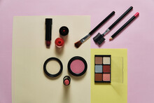 High Angle Of Assorted Decorative Cosmetics And Applicators Arranged On Three Colored Background In Studio