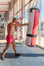 Side View Of Concentrated Male Boxer With Naked Torso And In Gloves Training With Punching Bag During Workout In Gym