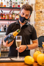 Male Bartender Pouring Sparkling Champagne In Glass Goblet Placed On Counter In Bar