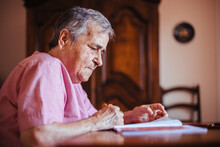 Side View Of A Senior Woman With Alzheimer's Mental Health Issues Painting On A Notebook Inside Her Home