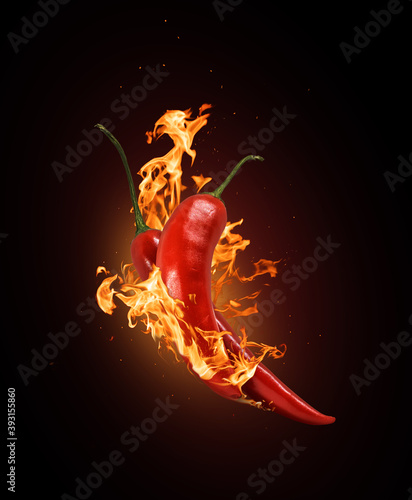 Fotografia Two red chili peppers in a burning flame close-up on a black background