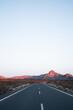 Spectacular scenery of empty asphalt roadway going toward mountain ridge illuminated by sunset sun in Tenerife