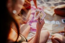 High Angle Back View Of Unrecognizable Young Woman Holding Cards While Playing Game With Friends On Beach