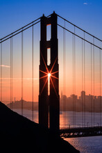 View Of Golden Gate Bridge With Silhouette Of Skyline In Background During Sunrise