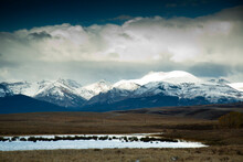 View Of Small Pond In Front Of Snow Covered Mountain Range In Montana