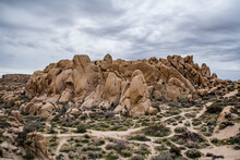 Massive Boulder Mound In Center Of Desert Landscape Under Cloudy Sky