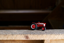 A Red Toy Tractor On A Ledge I...