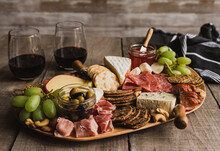 Close Up Of Charcuterie Board And Glasses Of Wine On Wooden Table.