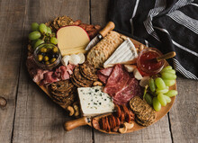 Close Up Of Charcuterie Board Of Meat, Cheese, Crackers On Wood Table.