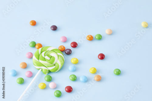 Canvas Print Top view closeup of multiple colorful lollipops and skittles on a pink backgroun