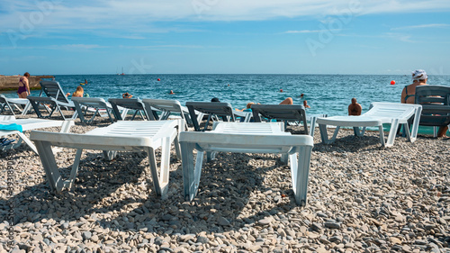 Fotografie, Obraz modern plastic sun loungers on the rocky Black Sea beach in the resort town of Sochi