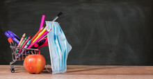 Back To School During Coronavirus Pandemic With Pencils, Crayons And Face Mask In Shopping Cart With Apple Against Chalkboard