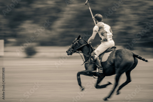 Fotografering Players riding polo ponies in a polo match at Kirtlington Park, Oxfordshire