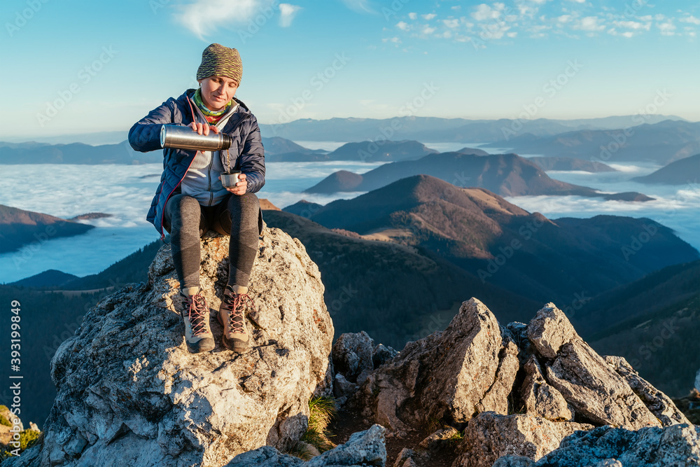 Fototapeta Active backpacker hiker woman sitting on the mountain summit cliff, pouring a tea from a thermos flask and enjoying mountains valley covered with clouds view. Successful summit climbing concept image.