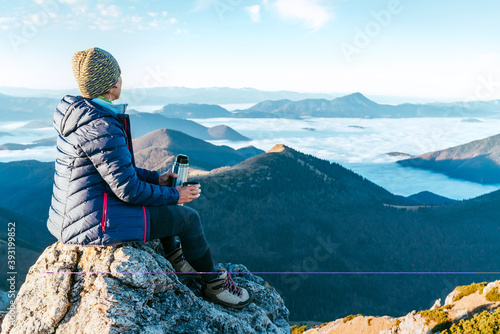 Fotomural Young hiker woman sitting on the mountain summit cliff and enjoying mountains valley covered with clouds view