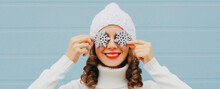 Winter Portrait Close Up Of Happy Smiling Woman Holding Snowflakes Covering Her Eyes Wearing A White Knitted Hat Over Blue Background
