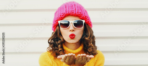 Fototapeta Winter portrait close up of young woman blowing red lips sending sweet air kiss