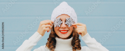 Fototapeta Winter portrait close up of happy smiling woman holding snowflakes covering her eyes wearing a white knitted hat over blue background obraz