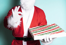 Closeup Shot Of Santa Claus Holding A Pizza Box With An Ok Hand Against A Blue Wall
