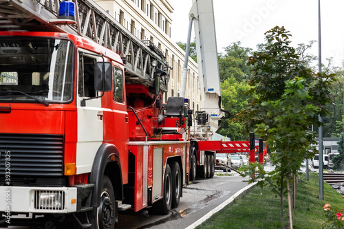 Fotografia, Obraz Many fire engine trucks with ladder and safety equipment at accident in highrise tower residential apartment or office building in city center