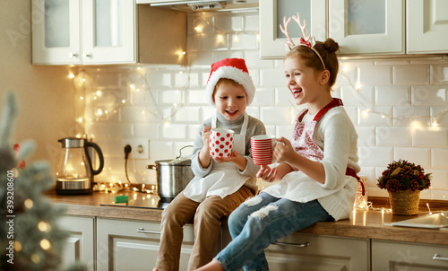 Fototapeta happy children on Christmas eve,   girl and boy drink hot cocoa drink that they baked together in cozy kitchen at home