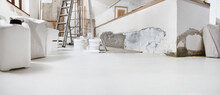 Low Angle Of Indoor Shot Of Construction Or Building Site Of Home Renovation With Tools With Paint Buckets And Primer Jerry Can On White Floor With Copy Space