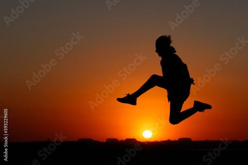 Fotografia silueta de chico a contraluz saltando el sol con los pelos al viento
