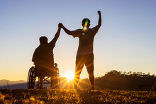 Silhouette Of Joyful Disabled Man In Wheelchair Raised Hands With Friend At Sunset