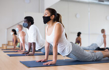 People In Protective Masks Practice Yoga In The Gym