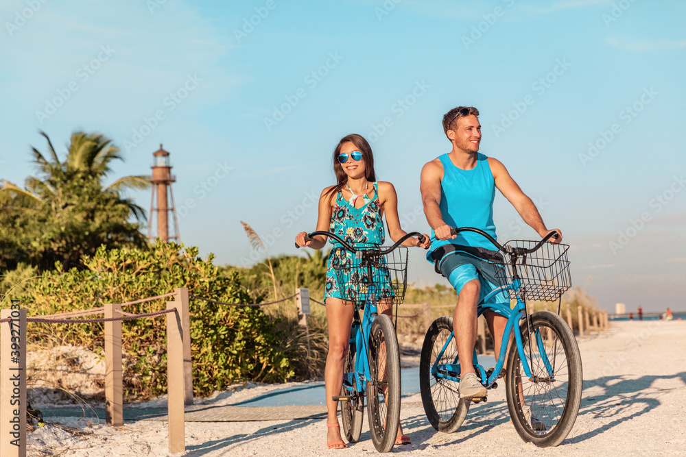 Fototapeta Biking activity couple tourists having fun doing outdoor sport on Florida beach vacation with rental bikes on Sanibel Island by the Lighthouse. woman with man friend riding bicycles outdoor lifestyle.