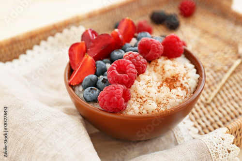 Obraz na plátně Bowl of tasty rice pudding with berries on wicker tray