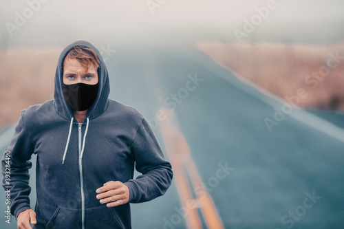 Fototapeta premium Sports mask endurance athlete runner running outside on road training while wearing facial covering in cold weather winter fog. Male jogger man jogging.