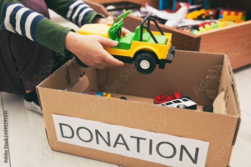 Obraz na plátně The boy is sorting his toys and puts toy car into the donation box