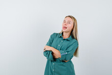 Blonde Girl Standing Arms Crossed, Sticking Tongue Out In Green Blouse And Looking Amused , Front View.